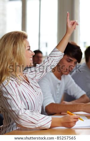 Female student raising her hand in university class