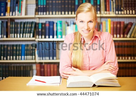 Female student reading a book and making notes