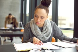 Female student reading a book for finding information. Young african american woman sitting at table doing assignments in university library.