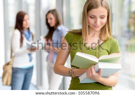 Female student reading book at high school library glass hall
