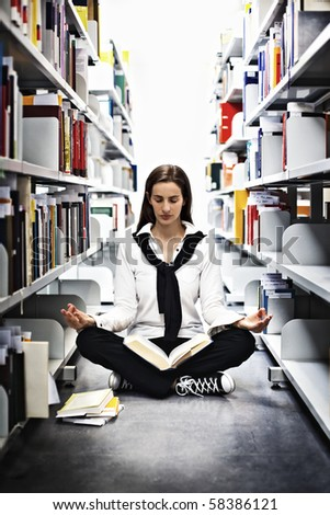 Female student sitting in Yoga pose in between bookshelves in modern university library and meditating over a book.