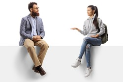 Female student sitting on a panel gesturing with hand and talking to a bearded man isolated on white background