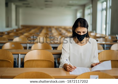 Female student taking an exam wearing a protective face mask in an empty amphitheater. Stressed student during COVID-19 outbreak.Coronavirus in-class test. Concerned woman having education evaluation Photo stock ©