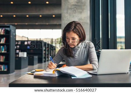 Female student taking notes from a book at library. Young asian woman sitting at table doing assignments in college library.
