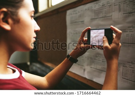 Female student talking a photograph of the notice board in high school. Girl taking a picture of exam timetable with her mobile phone in school. Stock photo ©