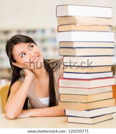 Female student with a pile of books at the library