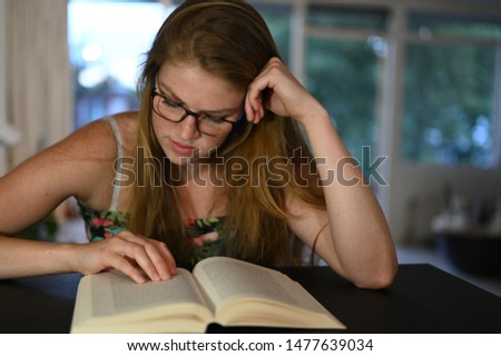 Female student with glasses is learning from her study book while sitting at home and is studying hard.