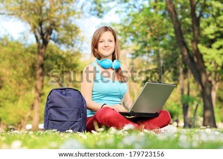 Female student with headphones relaxing in park and working on laptop