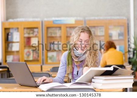 female student with laptop working in library