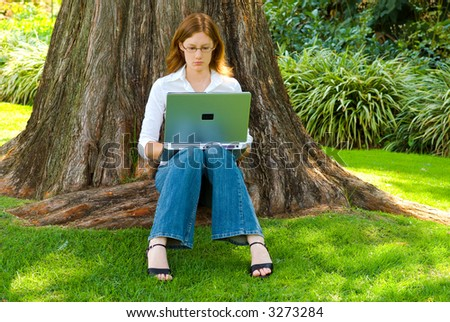 Female student with laptop working under large tree in park