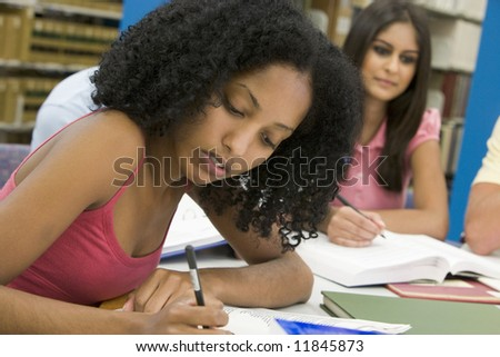 Female student working on essay in library