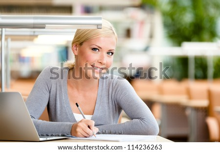 Female student working on the computer sitting at the desk. Process of studying