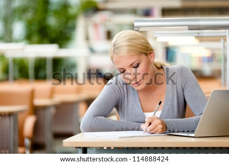 Female student working on the laptop sitting at the table. Process of learning