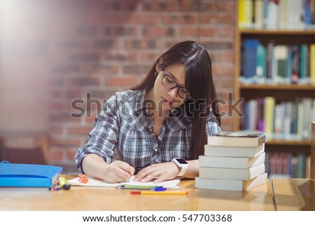 female student writing notes at ...