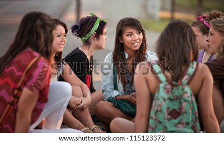 Female students talking outdoors on the sidewalk