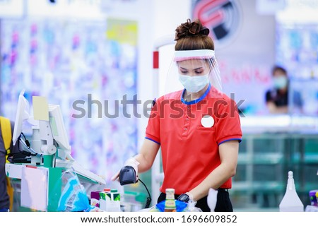 Photo of female supermarket cashier in medical protective mask and face shield working at supermarket. covid-19 spreading outbreak