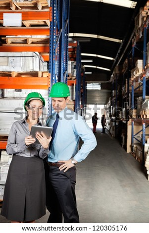 Female supervisor and colleague using digital tablet at warehouse