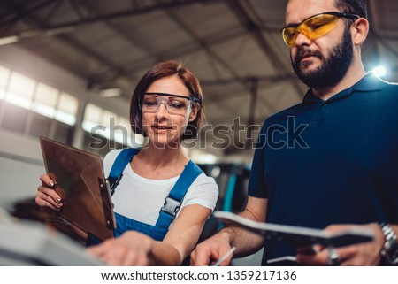 Female supervisor checking final product at factory with manual worker