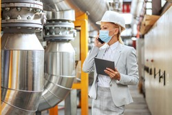 Female supervisor in suit, with helmet on head, with protective face mask holding tablet and speaking on the phone with important business partner while walking in heating plant during corona pandemic