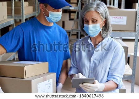 Female supervisor wearing face mask using digital tablet in warehouse talking to male courier holding shipping parcels boxes delivering packages. Covid 19 safety at work and safe shipping delivery.