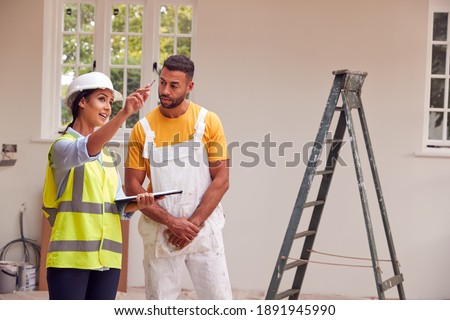 Female Surveyor With Clipboard Meeting With Decorator Working Inside Property Stok fotoğraf ©