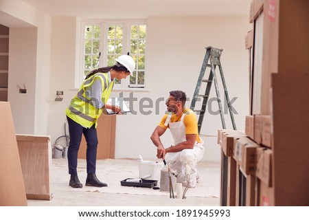Female Surveyor With Clipboard Meeting With Decorator Working Inside Property Foto stock ©