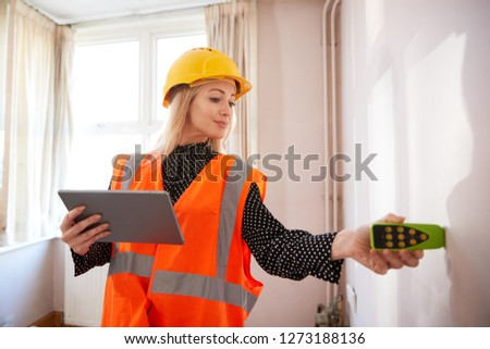 Female Surveyor With Digital Tablet Measuring Room With Laser Measure