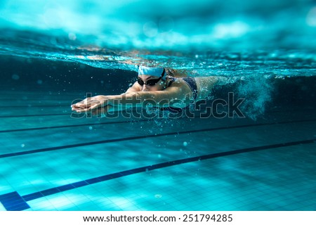 Female swimmer at the swimming pool.Underwater photo. #251794285