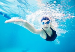 Female swimmer gushing through water in pool