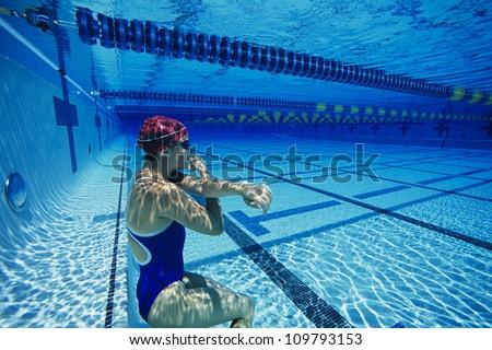 Female swimmer holding her breath underwater - stock photo