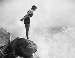 Female swimmer on rock above crashing surf