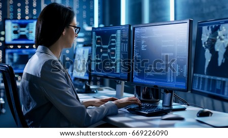 Female System Engineer Controls Operational Proceedings. In the Background Working Monitors Show Various Information.