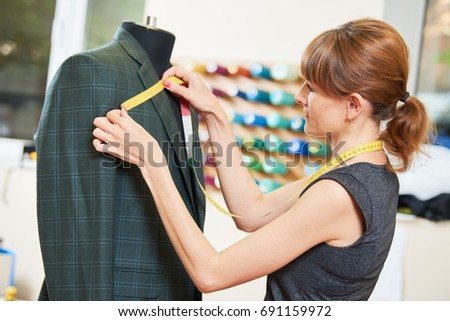 Female tailor works with male suit