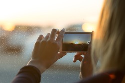 Female taking a photo of the sunset with a mobile phone through the window.