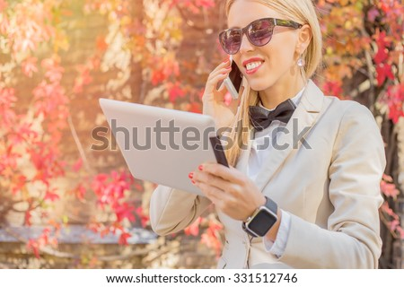 Female talking on the cellphone and looking at tablet  #331512746