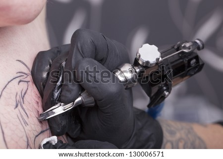 female tattoo artist at work. ( property release supplied includes tattooists' tattoo and artwork )