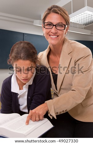Female teacher and schoolgirl working together in a classroom