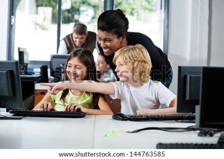 Female teacher assisting boy pointing on computer in lab at school