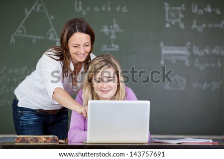 Female teacher assisting student in using laptop at desk in classroom