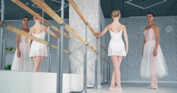 Female teacher explains exercise to little girl ballerina raising hand and leg near wooden barre in studio at dance lesson