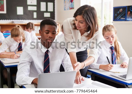 Female Teacher Helping Pupil Using Computer In Classroom