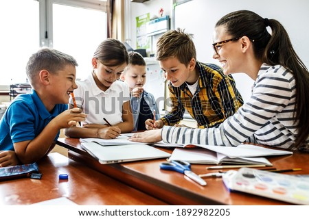 Female teacher helps school kids to finish they lesson.They sitting all together at one desk. Stock photo ©