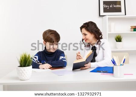 Female teacher helps teen boy to do his homework. Doing homework together.