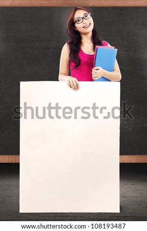 Female teacher holding empty copy space in front of chalkboard