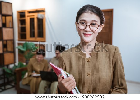 female teacher in civil servant uniform wearing glasses smiling while carrying a book with the background of a team of teachers while working from home