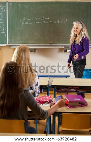 Female teacher in front of chalkboard in the classroom