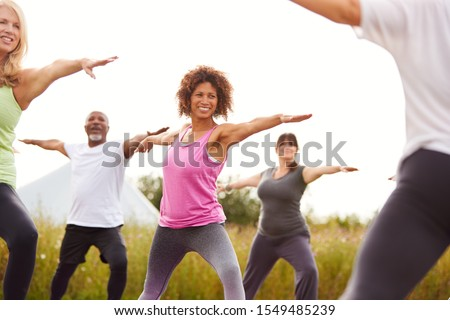 Female Teacher Leading Group Of Mature Men And Women In Class At Outdoor Yoga Retreat