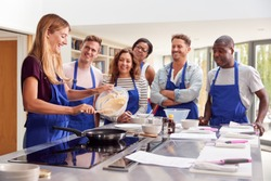 Female Teacher Making Pancake On Cooker In Cookery Class As Adult Students Look On