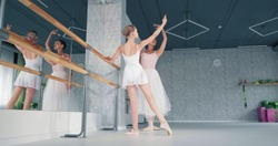 Female teacher shows ballet moves to preteen girl ballerina raising hand by wooden barre in studio at dance lesson
