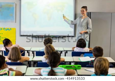 Female teacher teaching schoolchildren using projector screen in classroom